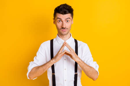 Photo pour Photo portrait of thoughtful curious man keeping fingers together got idea wearing suspenders isolated on vibrant yellow color background - image libre de droit