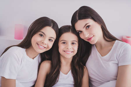 Photo pour Photo of pretty shiny three sisters sleepwear sitting bed having rest smiling inside indoors home room - image libre de droit