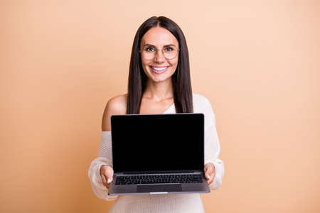 Foto de Photo of young cheerful woman present show laptop recommend advert isolated over beige color background - Imagen libre de derechos
