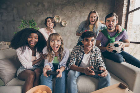 Photo pour Portrait of attractive cheerful friends sitting on sofa having fun playing video game in house loft brick style interior indoors - image libre de droit