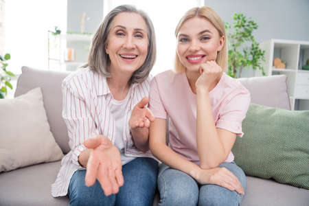 Photo pour Portrait of two attractive cheerful women sitting on cozy divan calling video talking free time at home indoor - image libre de droit