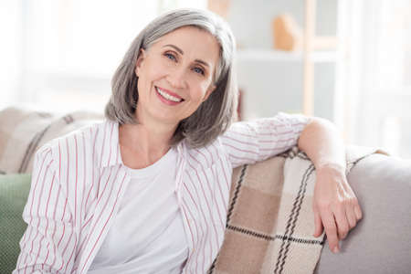 Photo pour Photo of happy cheerful old pretty lady sit couch smile good mood smile indoors inside house home apartment - image libre de droit
