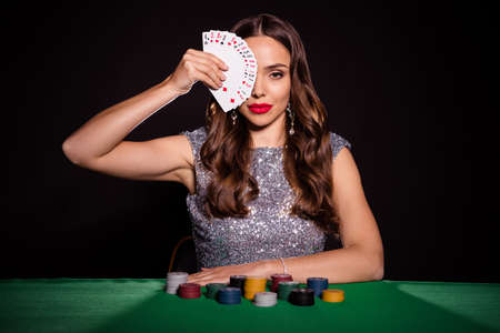 Photo pour Photo of serious stunning young woman hold cards cover face sit poker table player isolated on black color background - image libre de droit