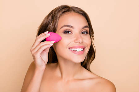 Photo pour Photo of young beautiful smiling woman applying foundation on cheek with beauty blender isolated on beige color background - image libre de droit
