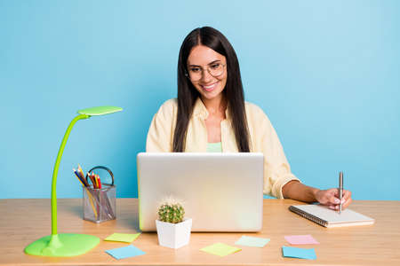 Photo pour Photo of cheerful happy young brunette lady look laptop sit desk work wtite note isolated on pastel blue color background - image libre de droit