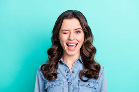Photo pour Photo of charming funny young woman wear jeans shirt open mouth winking isolated turquoise color background - image libre de droit