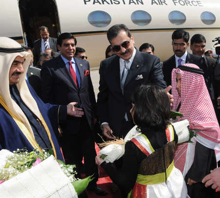 KUWAIT/KUWAIT.   Two Kuwaiti children presenting bouequet  to Prime Minister Syed Yusuf Raza Gilani at Amiri Terminal at Kuwait Airport on February 14, 2011.