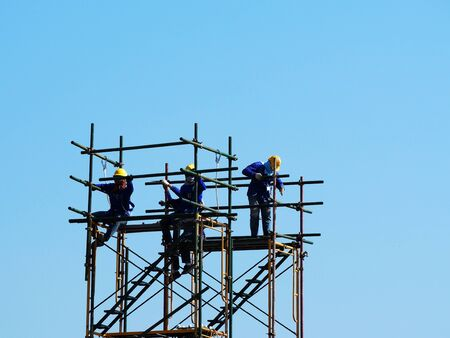 Photo pour Construction workers working on scaffolding, Man Working on the Working at height with blue sky at construction site - image libre de droit