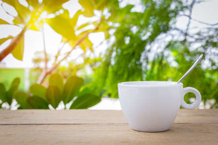Photo pour A white coffee cup with spoon is placed on a wooden plate and on the landscape nature background. - image libre de droit