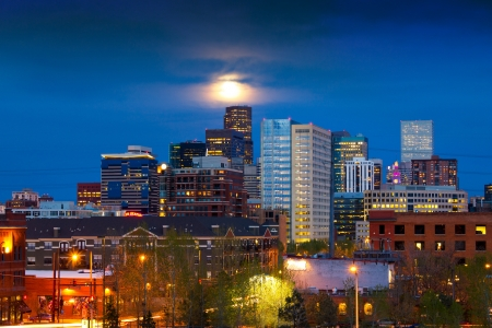 Denver skyline at dusk with the full moon rising above