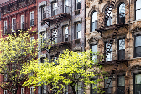 Foto de Sunlight shines on trees in front of historic old buildings on 3rd Avenue in the East Village of Manhattan, New York City NYC - Imagen libre de derechos