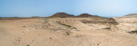 sand dunes and rocks of Fuerteventura island with volcanoes in the background, Canary