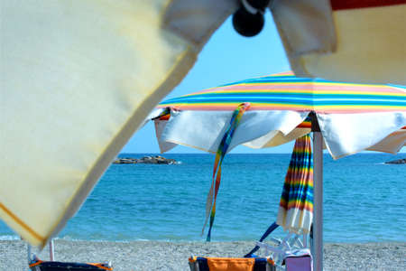 relaxing day at the beach under the colorful beach umbrella by the sea