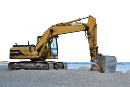 excavator that is working on the beach to smooth the sand before the start of the summer season