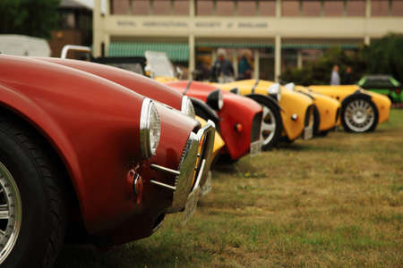 Red and yellow sports cars lined up at a car show in the UK