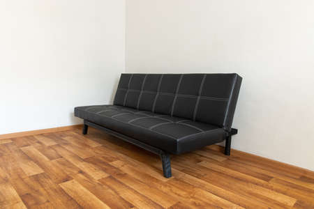 Photo pour Modern black leather convertible sofa bed, wooden floor. Empty waiting room with a modern black sofa - image libre de droit