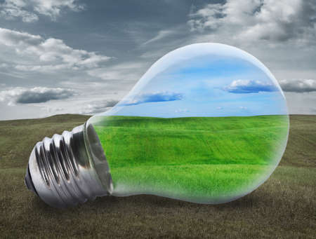 Light bulb with a green field inside. Environment, eco technology and energy concept.