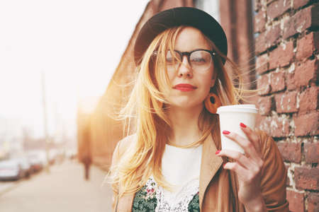 Stylish woman in the street drinking morning coffee
