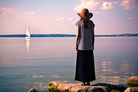 woman standing alone at sea coast and looking at ship
