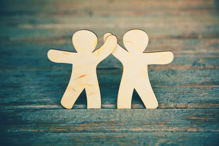 Wooden little men holding hands on wooden boards background. Symbol of friendship, love and teamwork