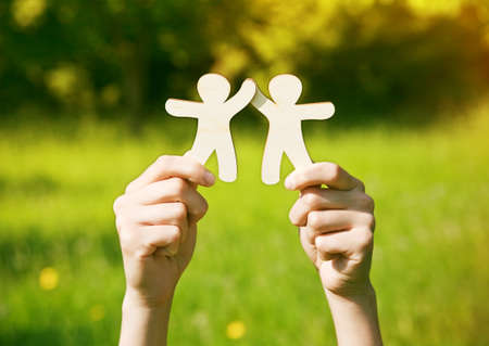 Hands holding wooden little men on natural background. Symbol of friendship, love, teamwork or ecology concept