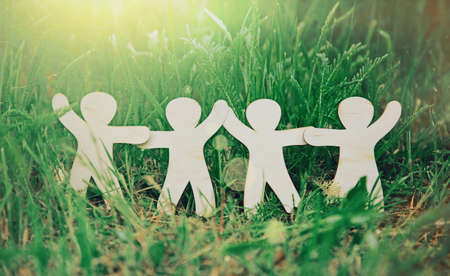 Wooden little men holding hands in summer grass. Symbol of friendship, family, teamwork or ecology conceptの写真素材