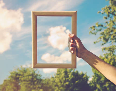 Photo pour Hand holding a wooden frame on cloud background. Care, safety, memory or painting concept. - image libre de droit
