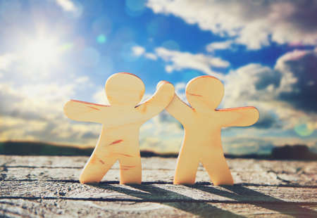 Wooden little men holding hands on sky and sun background. Symbol of friendship, love and teamwork