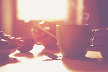 fresh breakfast with hot coffee and browsing smartphone in morning sunlight