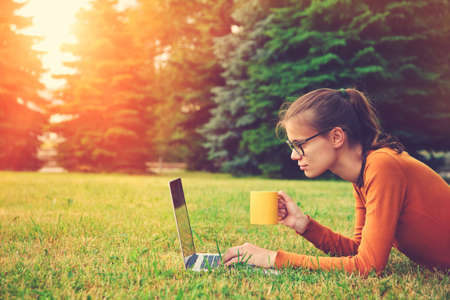 girl lying on the grass and using laptop and typing with coffee or tea mug. copy space