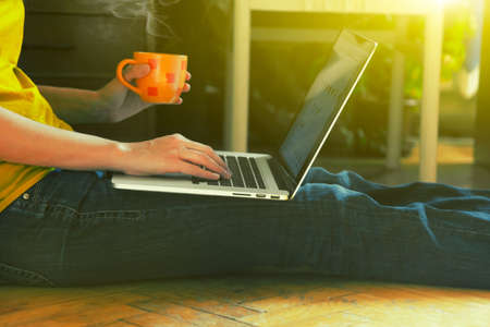 Photo pour laptop and coffee cup in girls hands sitting on a wooden floor - image libre de droit
