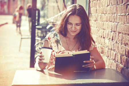 smiling girl sitting at summer terrace in street with morning coffee and reading book