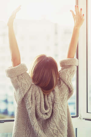 Photo for Woman near window raising hands facing the sunrise at morning - Royalty Free Image