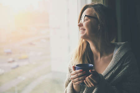 Photo pour cheerful girl drinking coffee or tea in morning sunlight near window - image libre de droit