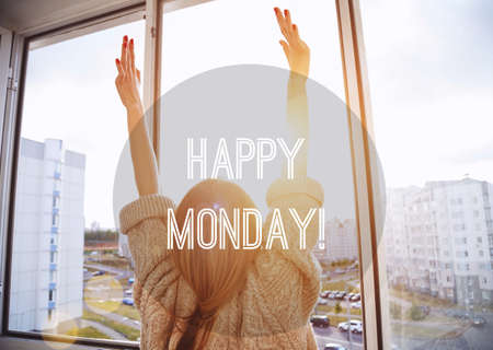Woman facing the sunrise with raising hands. Happy Monday motivational text