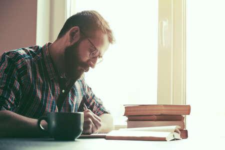 Foto de Bearded man writing with pen and reading books at table - Imagen libre de derechos