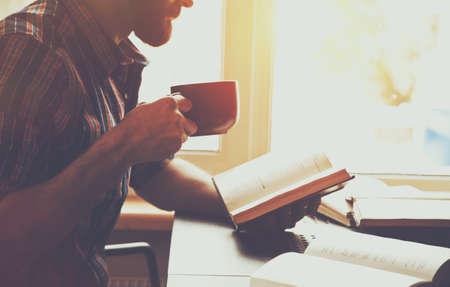 Photo pour bearded man reading book with coffee or tea - image libre de droit