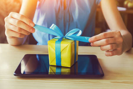Foto de hands with gift box and digital tablet. online shopping concept - Imagen libre de derechos