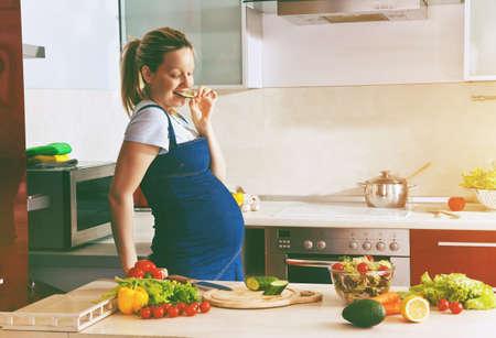 Foto de happy pregnant woman on kitchen making healthy salad - Imagen libre de derechos