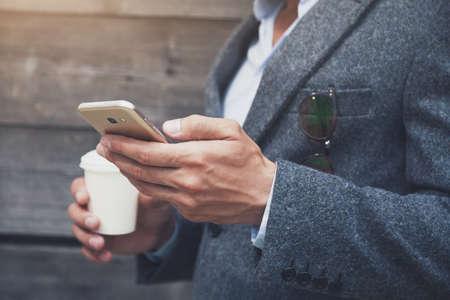 Foto de businessman hand holding morning coffee and reading phone - Imagen libre de derechos