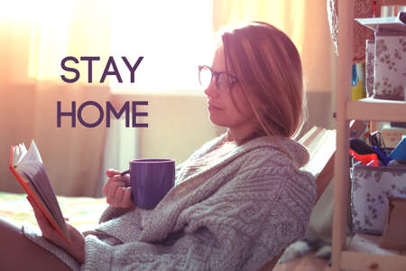 Photo pour Pretty girl reading book with coffee and text Stay home. Home isolation and quarantine during coronavirus covid-19 pandemic. - image libre de droit