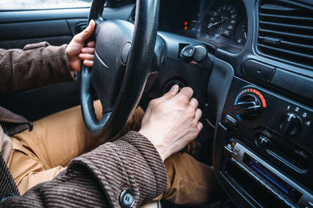 Man driver hand puts car key to keyhole to start his automobile, toned