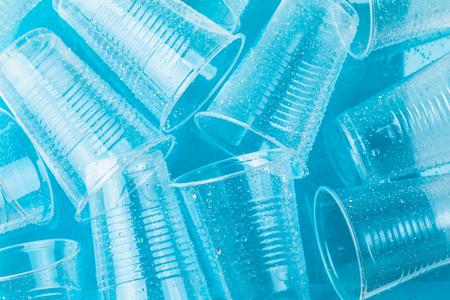 Photo pour Empty transparent disposable plastic glasses in drops of water on bright blue background,  top view - image libre de droit