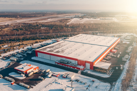 Photo pour Aerial view of warehouse storages or industrial factory or logistics center from above. Top view of industrial buildings and trucks in winter landscape - image libre de droit