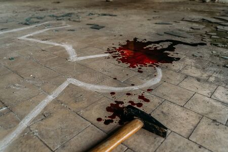 Photo pour Crime Scene with Hammer on dirty floor Weapon of Killing and white chalk Outline of Murdered Body with Blood, close up - image libre de droit