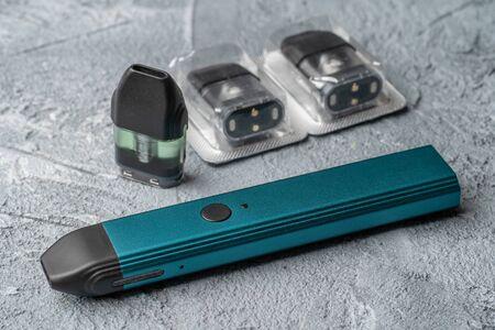Foto de Vape pod system and replacement cartridges filled with e-juice or liquid with salt nicotine, new vape pen device, close up. - Imagen libre de derechos