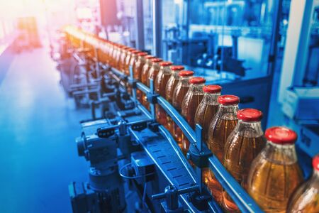 Photo for Conveyor belt, factory interior in blue color and bottles with juice, industrial production line, toned - Royalty Free Image
