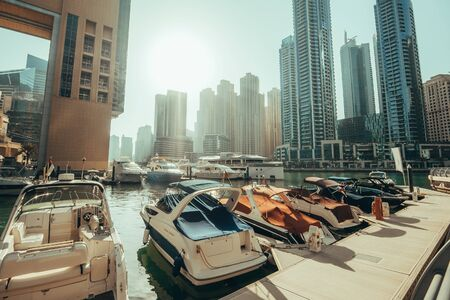 Photo pour Dubai Marina skyscrapers panorama on background and luxury yacht with boats in water canal, Dubai, United Arab Emirates, toned - image libre de droit
