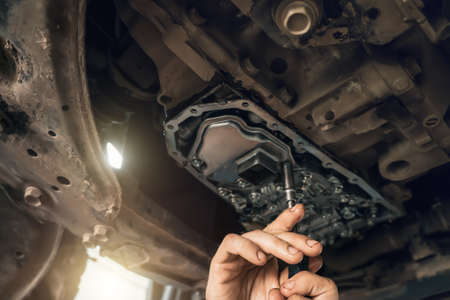 Photo pour CVT gearbox close up, worker hands changing oil and making maintenance in new modern variator automatic transmission on SUV in Car Service. - image libre de droit