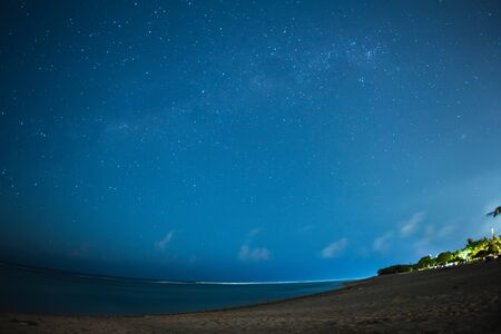 Starry night on the beach with sky, beach and sun beds